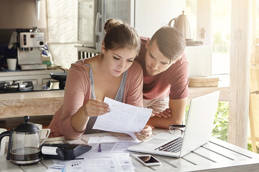 couple at the kitchen table reviewing finances and examining bills