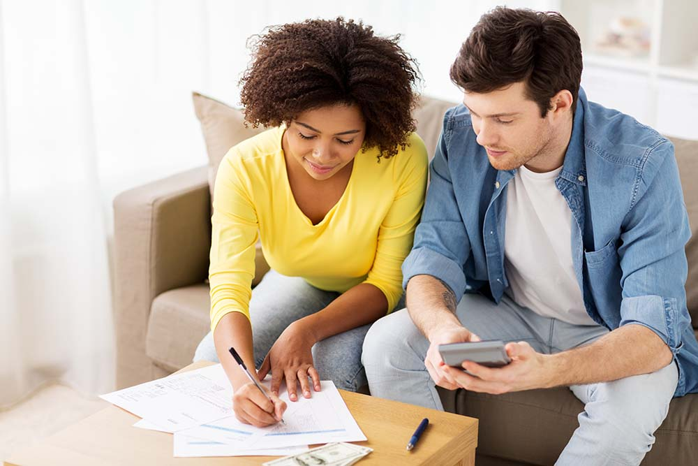 man and woman sat on a couch, reviewing financees and bills with a calculator