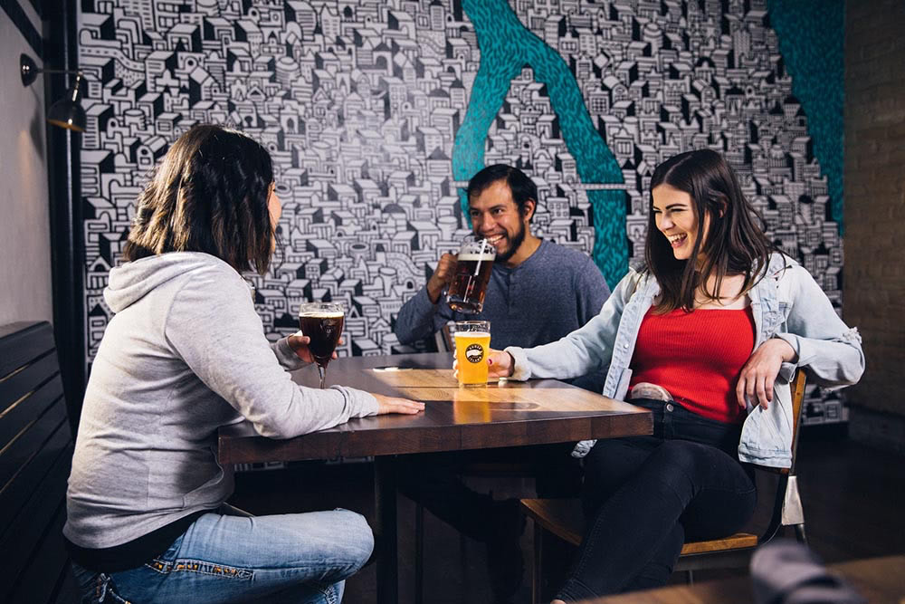 three smiling friends gathered round a table in a bar having drinks
