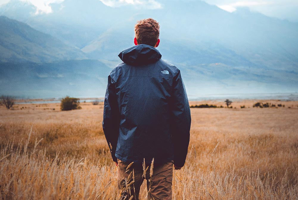 man, wearing a coat, stood in a field looking at a view of mountains