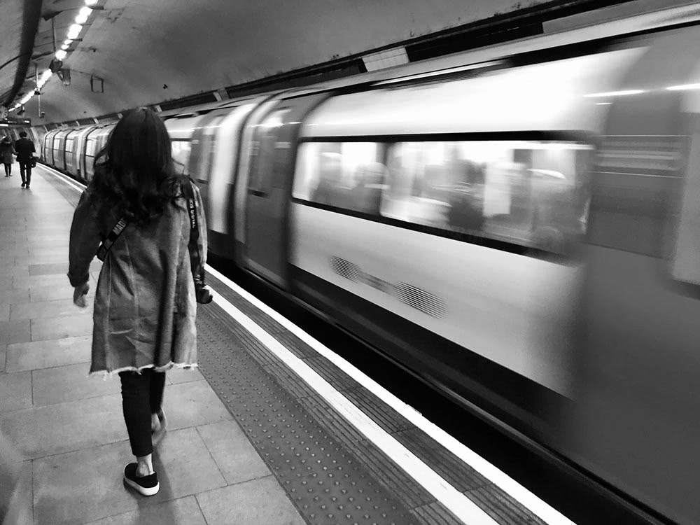 black and white photo of woman walking on a tube platform next to a moving train
